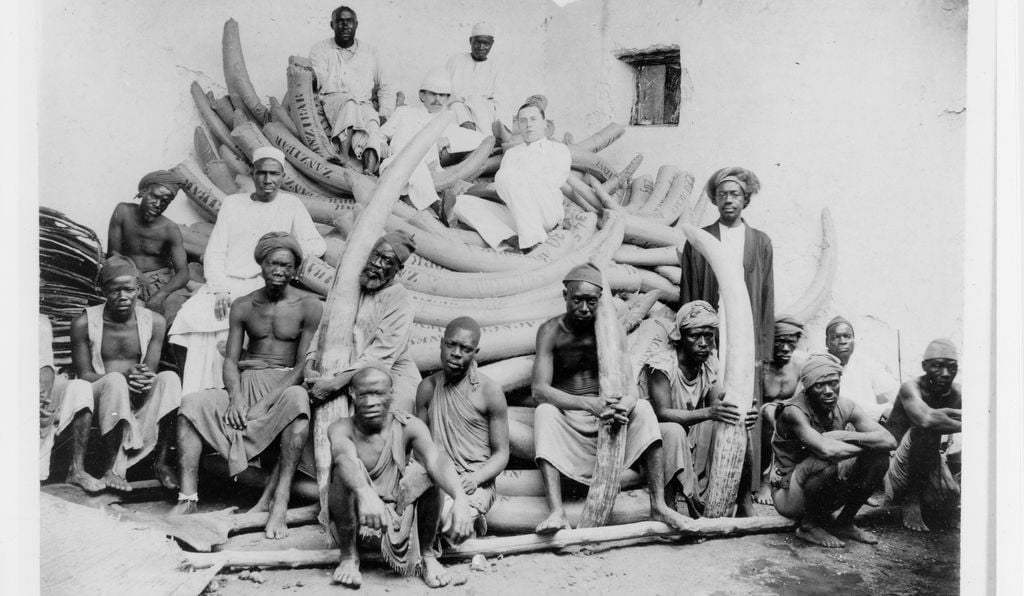 Ernst Moore, a Connecticut ivory trader, poses among Arab and Indian merchants and African caravan tusk porters in Zanzibar around 1900.